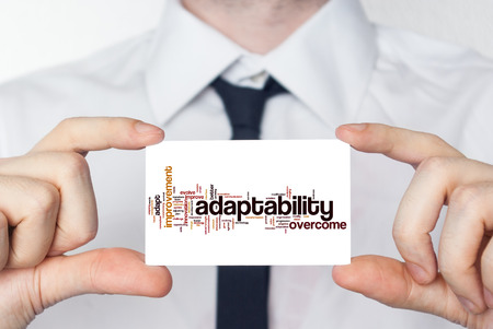 Adaptability. Businessman in white shirt with a black tie showing or holding business card photo