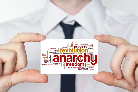 anarchism: Anarchy. Businessman in white shirt with a black tie showing or holding business card Stock Photo
