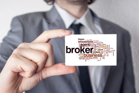 Broker. Businessman in suit with a black tie showing or holding business card Stok Fotoğraf