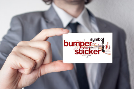 Bumper sticker. Businessman in suit with a black tie showing or holding business card 스톡 콘텐츠