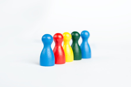Diversity concept with colorful game figurines in line on white photo