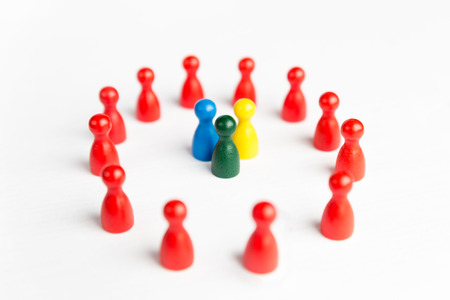 Team surrounded by adversity or praised for being different concept with figurines Stock Photo
