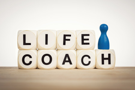 Coaching concept: Blue pawn next to word Life coach spelled by toy dice