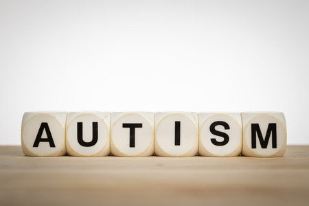 Term Autism spelled out with toy dice on a board photo