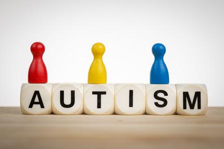 Concepto Autismo: Peones en diferentes colores en la parte superior de los dados de juguete Foto de archivo