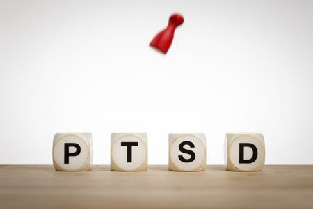 traumatic: Posttraumatic stress disorder concept: Word PTSD and a falling pawn in motion Stock Photo