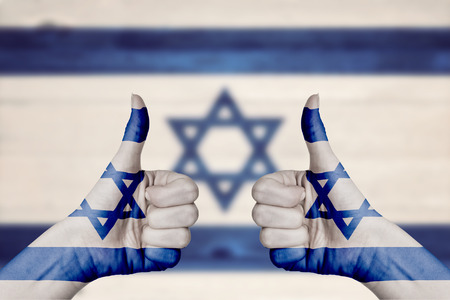 Israel flag painted on female hands thumbs up with blurry wooden background photo