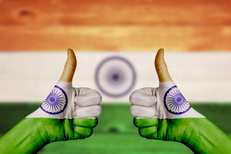 two thumbs up: India flag painted on female hands thumbs up with blurry wooden background