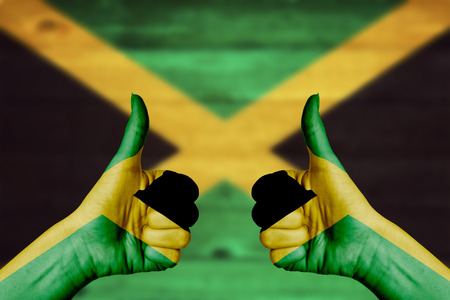 jamaica: Jamaica flag painted on female hands thumbs up with blurry wooden background Stock Photo