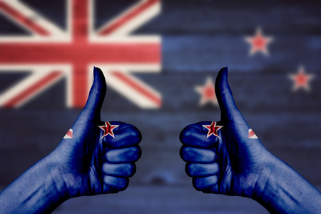 two thumbs up: New_Zealand flag painted on female hands thumbs up with blurry wooden background