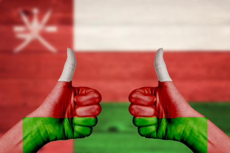 oman background: Oman flag painted on female hands thumbs up with blurry wooden background