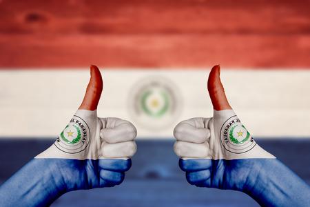 bandera de paraguay: Paraguay bandera pintada en las manos de pulgar arriba con fondo de madera borrosa Foto de archivo