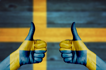Sweden flag painted on female hands thumbs up with blurry wooden background photo