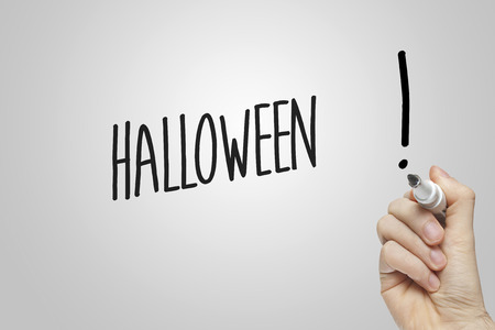 Hand writing halloween on grey background photo