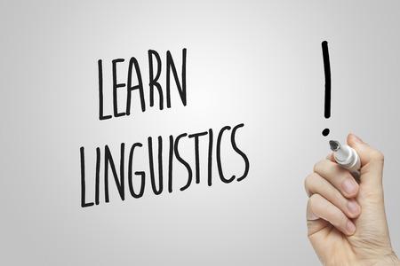 linguistics: Hand writing learn linguistics on grey background Stock Photo