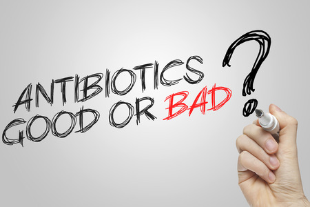 Hand writing antibiotics good or bad on grey background