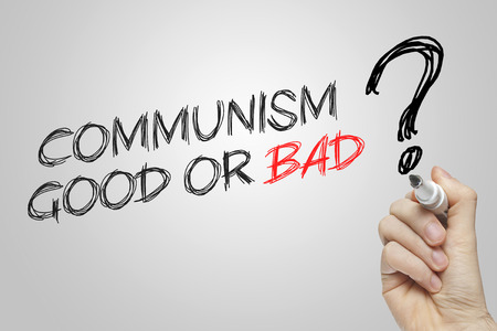 communism: Hand writing communism good or bad on grey background