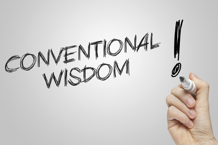 conventional: Hand writing conventional wisdom on grey background