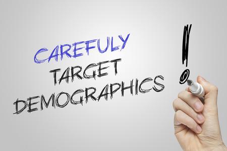 demographics: Hand writing carefuly target demographics on grey background