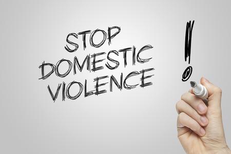 violencia intrafamiliar: Escritura de la mano a detener la violencia doméstica en el fondo gris