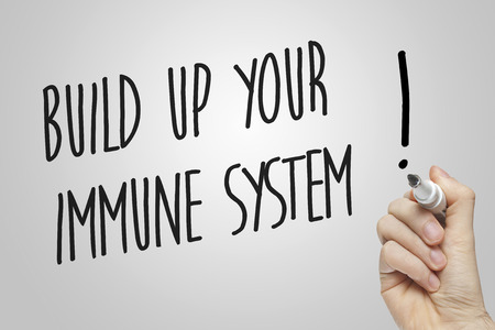 Hand writing build up your immune system on grey background