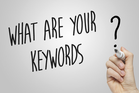 Hand writing what are your keywords on grey background Фото со стока