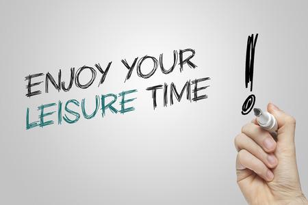 Hand writing genießen Sie Ihre Freizeit auf grauem Hintergrund Standard-Bild