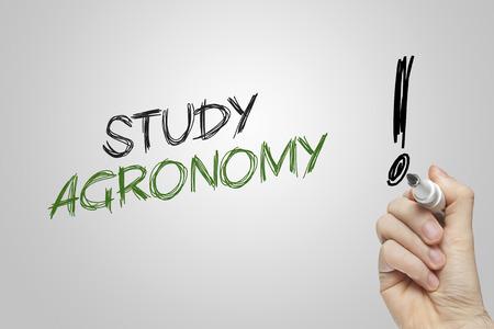 agronomy: Hand writing study agronomy on grey background