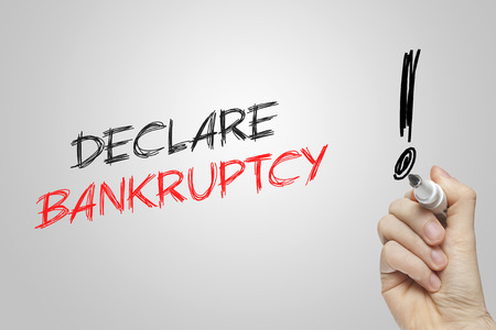declare: Hand writing declare bankruptcy on grey background