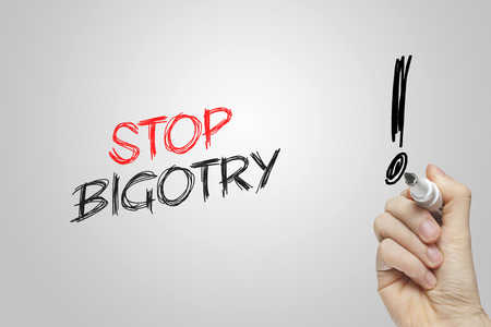 bigotry: Hand writing stop bigotry on grey background Stock Photo
