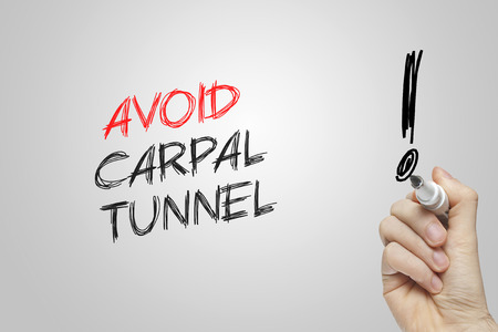 carpal tunnel: Hand writing avoid carpal tunnel on grey background Stock Photo