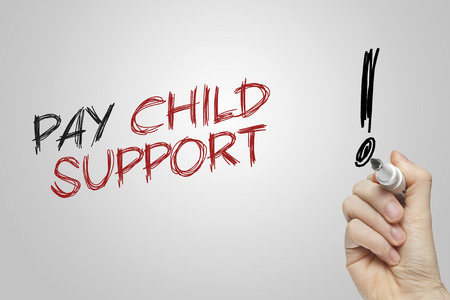 Hand writing pay child support on grey background