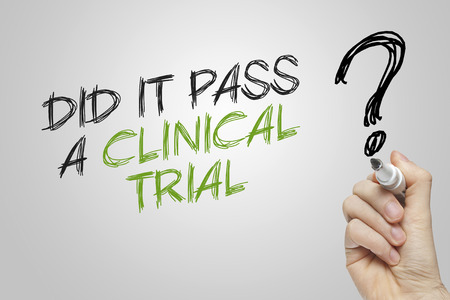 clinical trial: Hand writing did it pass a clinical trial on grey background Stock Photo
