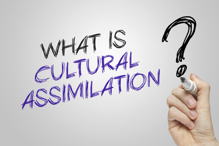 assimilation: Hand writing what is cultural assimilation on grey background