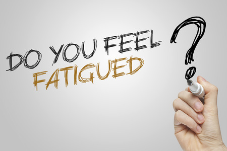 fatigued: Hand writing do you feel fatigued on grey background Stock Photo
