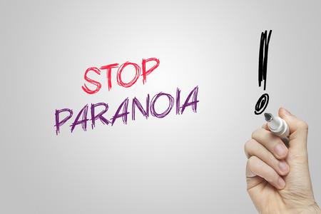 paranoia: Mano scrittura fermata paranoia su sfondo grigio