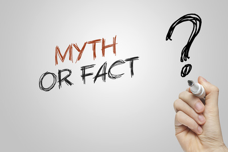 Hand writing myth or fact on grey background