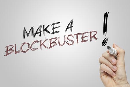 blockbuster: Hand writing make a blockbuster on grey background