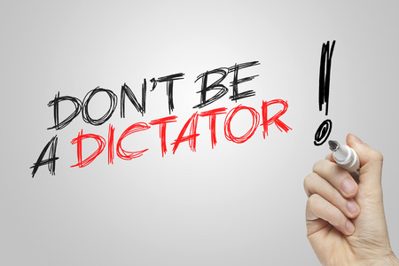 dictator: Hand writing dont be a dictator on grey background