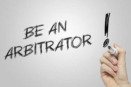 arbitrator: Hand writing be an arbitrator on grey background