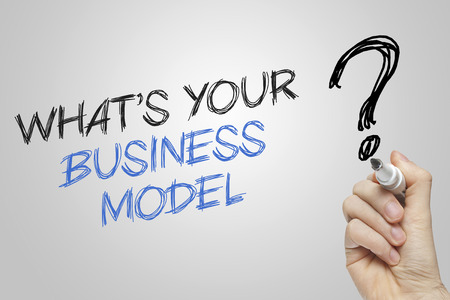 business model: Hand writing whats your business model on grey background