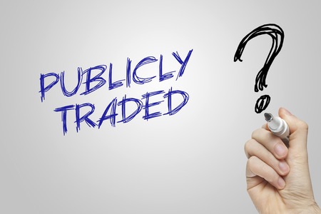 traded: Hand writing publicly traded on grey background