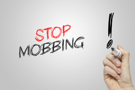 mobbing: Hand writing stop mobbing on grey background