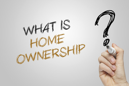 home ownership: Hand writing what is home ownership on grey background
