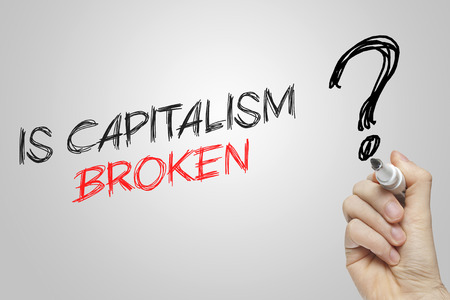 capitalism: Hand writing is capitalism broken on grey background