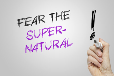 supernatural: Hand writing fear the supernatural on grey background Stock Photo