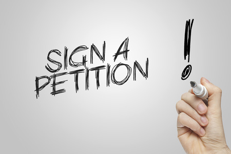 Hand writing sign a petition on grey background