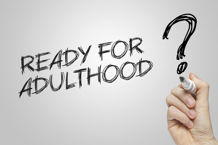 adulthood: Hand writing ready for adulthood on grey background