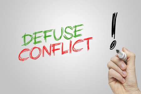 defuse: Hand writing defuse conflict on grey background