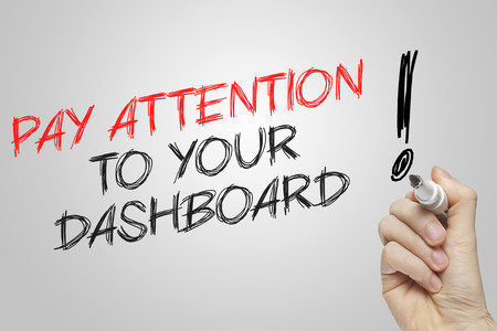 pay attention: Hand writing pay attention to your dashboard on grey background Stock Photo